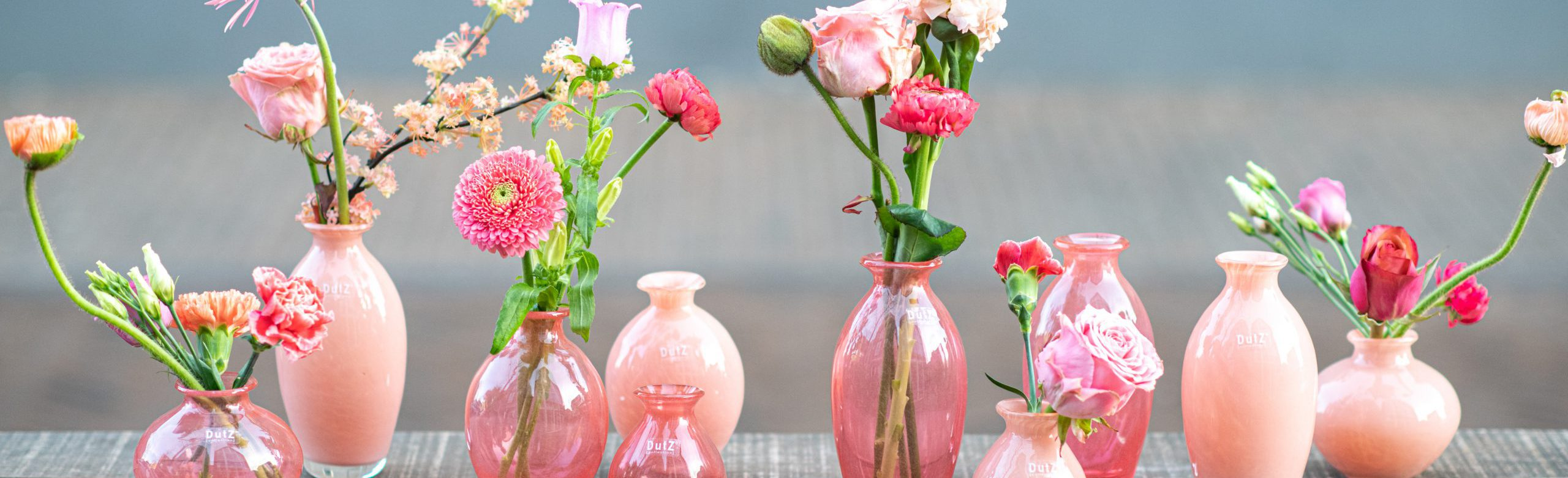 Nadiel vases in different shades of pink on a table. Filled with pink flowers