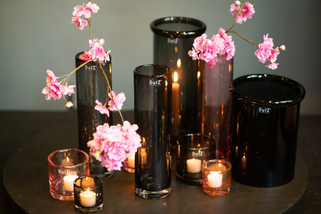 Grey and apricot cylinders filled with small candles and branches