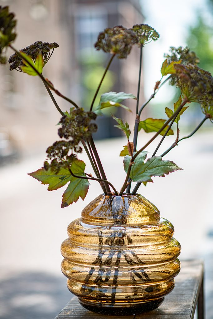 Honey barrel vase in the colour amber with a large branch in it