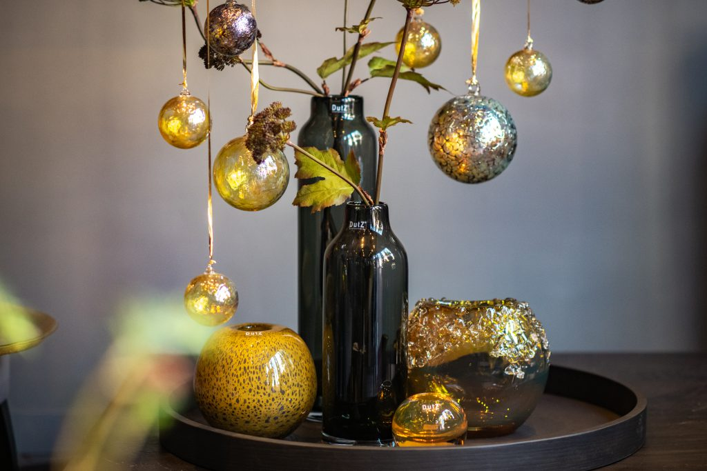 Longo vases in the colour grey filled with branches and on that branches are decorative balls in gold colours. On the left is a golden ball vase and on the right a Bumpy vase in the colour gold