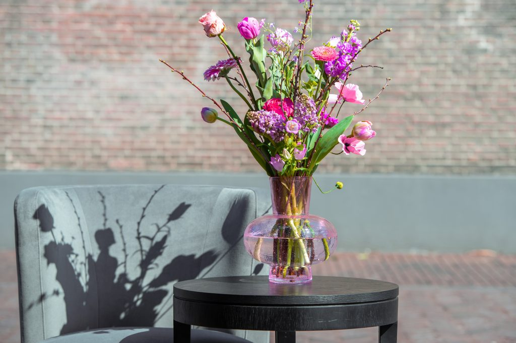 Modest vase in the colour apricot with an colourful bouquet on a wooden table