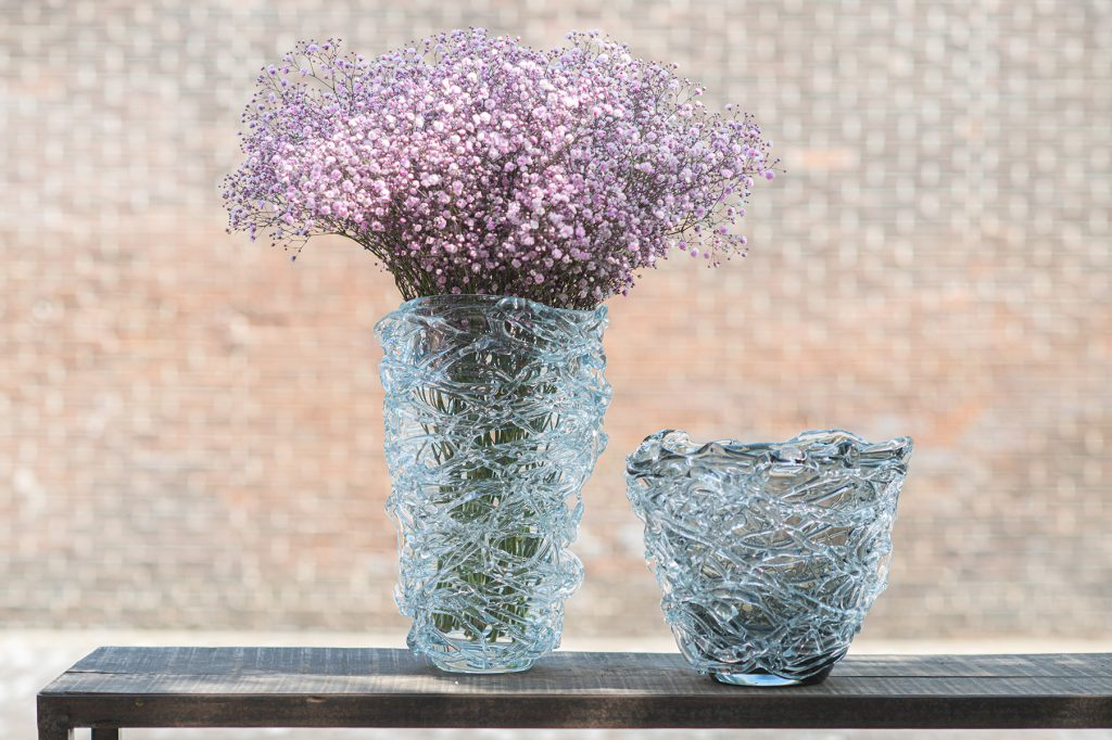 Vases nest in 2 sizes. The right one is filled with a bunch of flowers